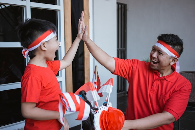 Father and son high five while decorating bicycle