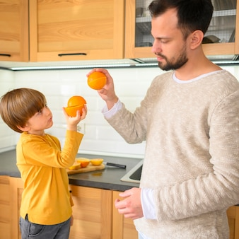 Father and son high five with oranges