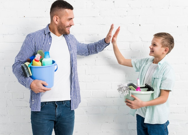 Father and son high-fiving each other while holding cleaning products