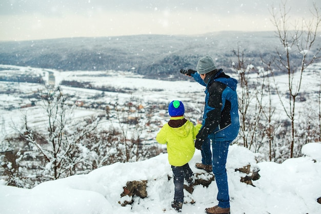 Father and son hiking in winter mountains child looking through monoculars on snowy slopes