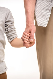 Father and son holding hands on white