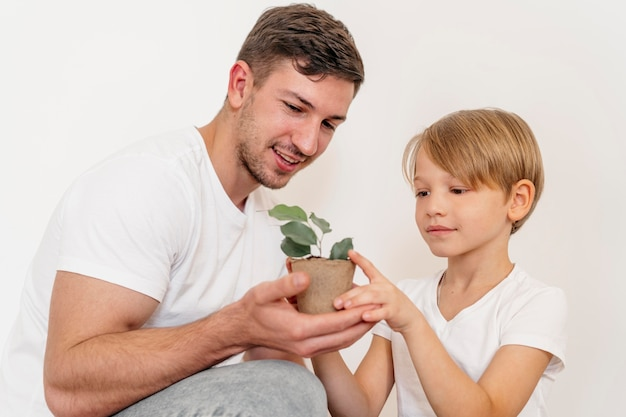 Father and son holding pot of plant and learning about planting