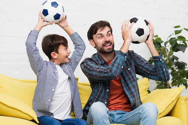 Father and son holding soccer balls