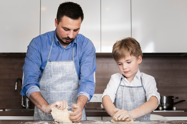 Father and son at home rolling dough