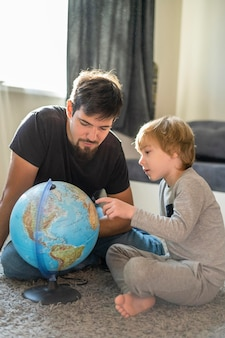 Father and son at home with earth globe