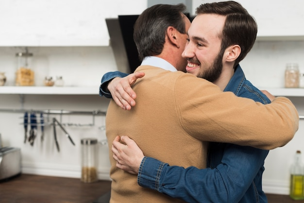 Father and son hugging in kitchen