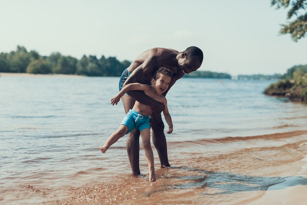 Father and son is plays in water on river shore