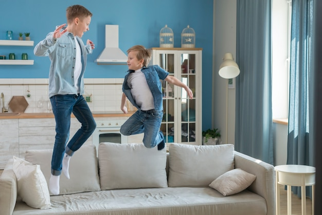 Father and son jumping on the sofa