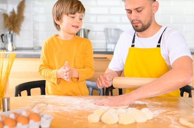 Father and son knead the dough with bare hands