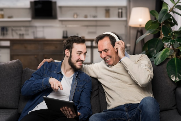 Father and son laughing and looking at tablet