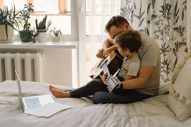 Father and son learn to play the acoustic guitar in an online lesson