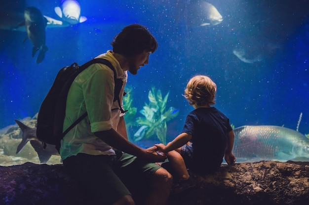Father and son look at the fish in the aquarium in oceanarium