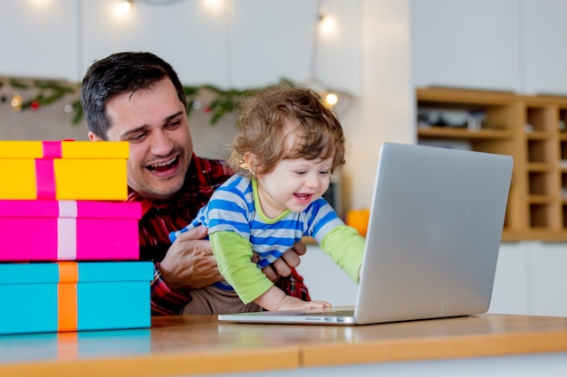 Father and son looking for christmas gifts in laptop computer sitting in kitchen at home.