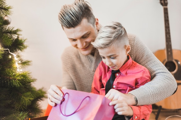 Father and son looking into bag next to christmas tree