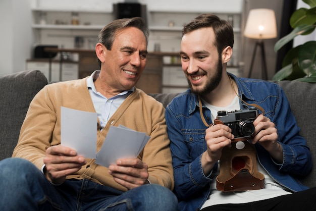 Father and son looking at photos in living room