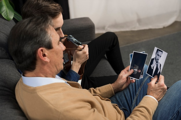 Father and son looking at pictures in living room