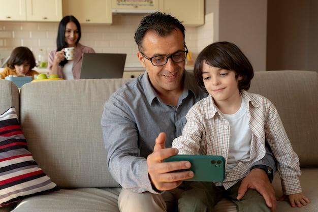Padre e figlio che guardano uno smartphone a casa