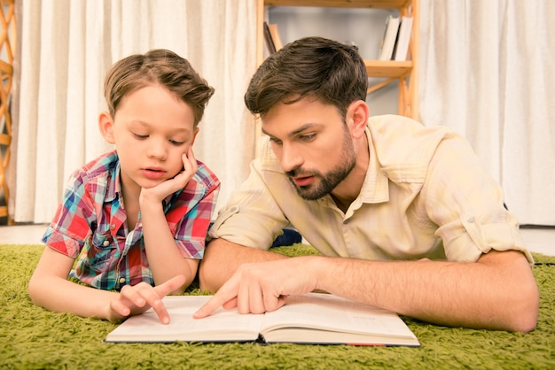Father and son lying on carpet while teaching reading