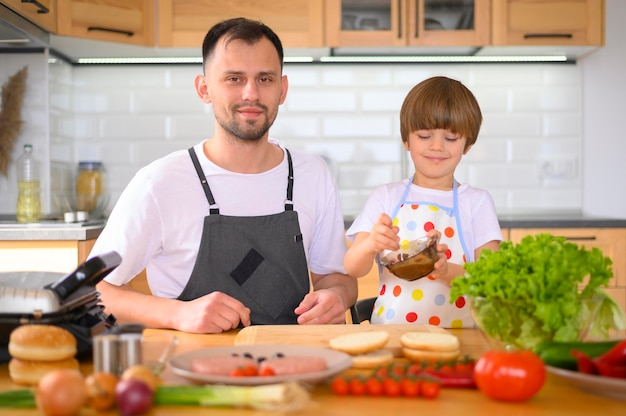 Padre e figlio che producono un hamburger vista frontale