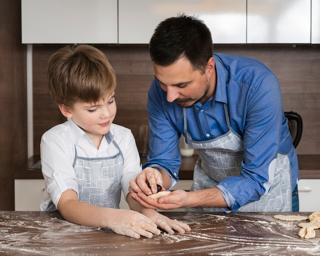 Father and son making shapes of dough
