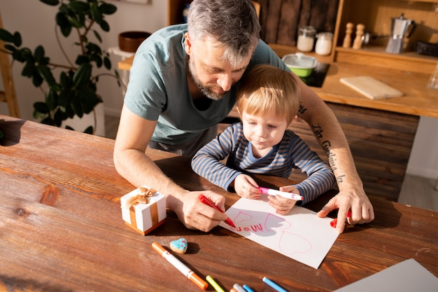Father and son making valentines card for mother