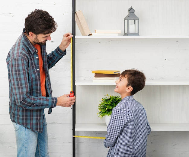 Father and son measuring a shelf