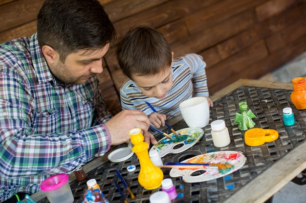 Father and son paint brush