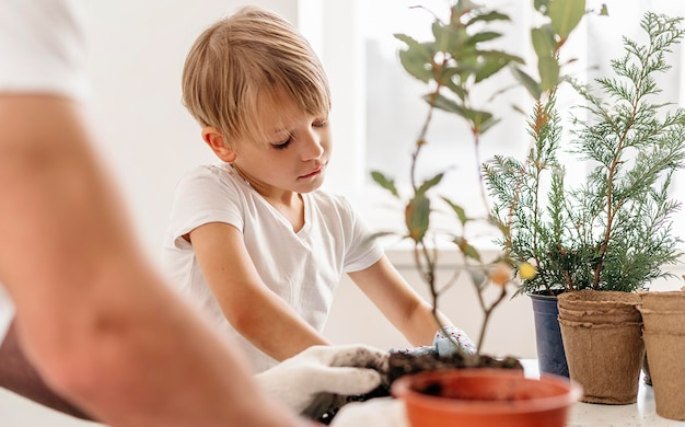 Father and son planting plants together at home