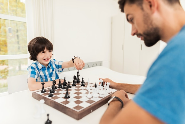 Father and son play chess in their home.