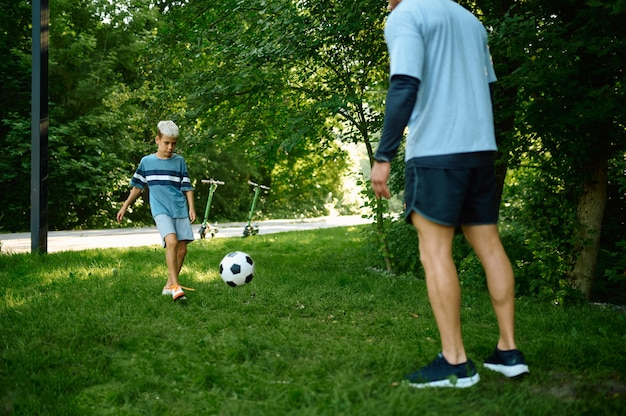 Father and son play football on the grass outdoors. the family leads a healthy lifestyle, morning fitness workout in summer park