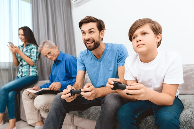 Father and son play game on game console.