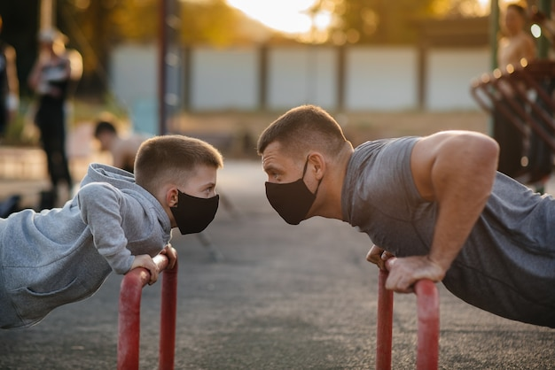 Father and son play sports on the sports field in masks during sunset. healthy parenting and healthy lifestyle.