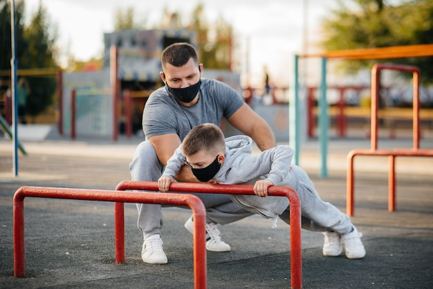 Father and son play sports on the sports field in masks