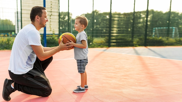 Father and son playing on the basketball field long view