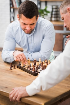 Father and son playing chess on table