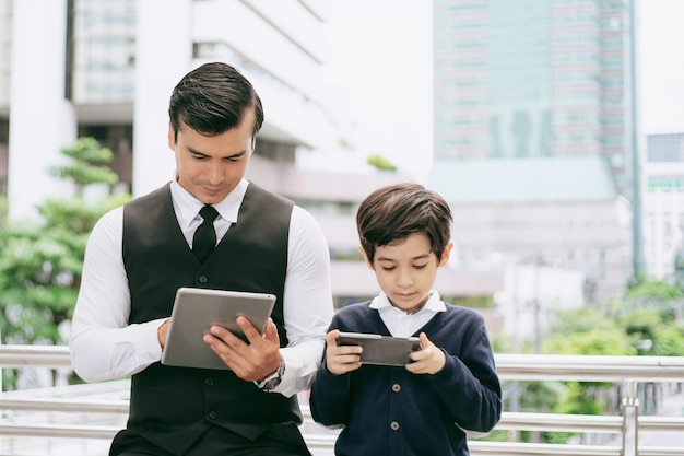 Father and son playing game smart phone together on business district urban, dad and son happy family.