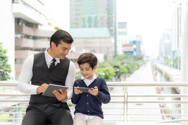 Father and son playing game smart phone together, dad and son happy family concept
