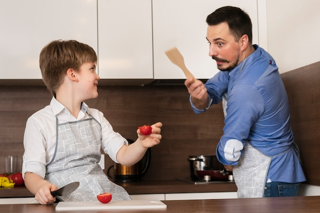Father and son playing in kitchen while cooking