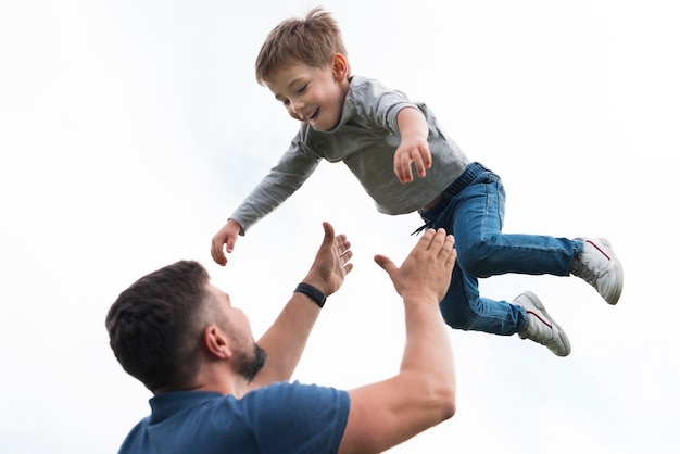 Father and son playing low view