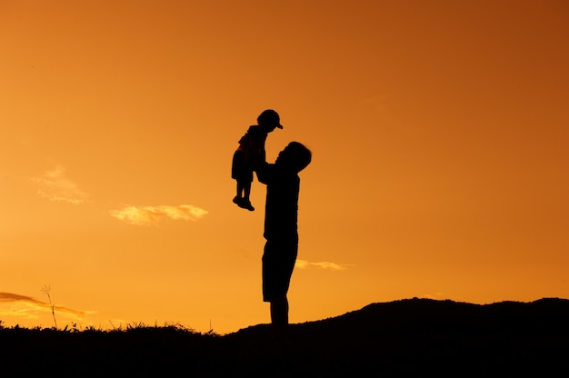 A father and son playing outdoors at sunset