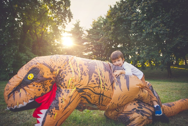 Father and son playing at the park with a dinosaur costume, having fun with the family outdoor