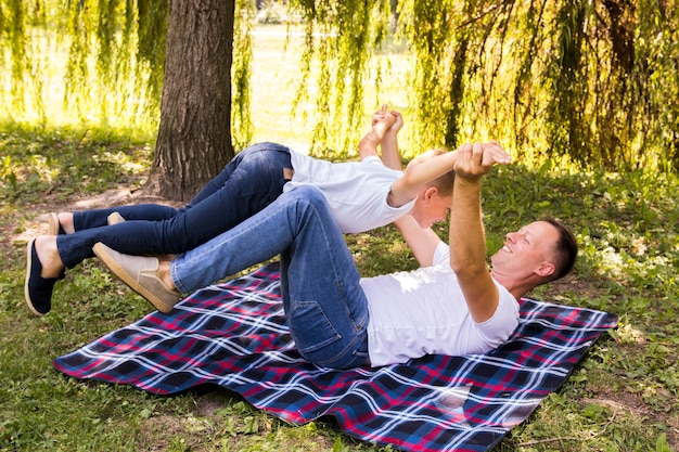 Father and son playing on picnic blanket