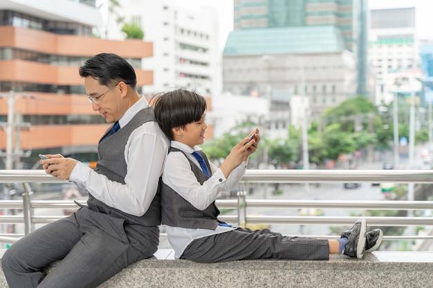 Padre e figlio che giocano insieme smart phone sul quartiere degli affari urbano