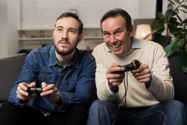Father and son playing videogames in living room