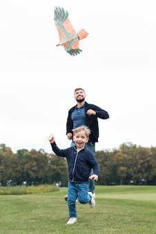 Father and son playing with kite front view