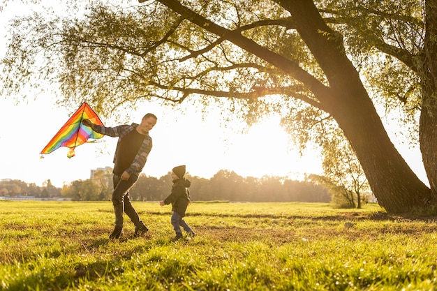 Father and son playing with a kite in park