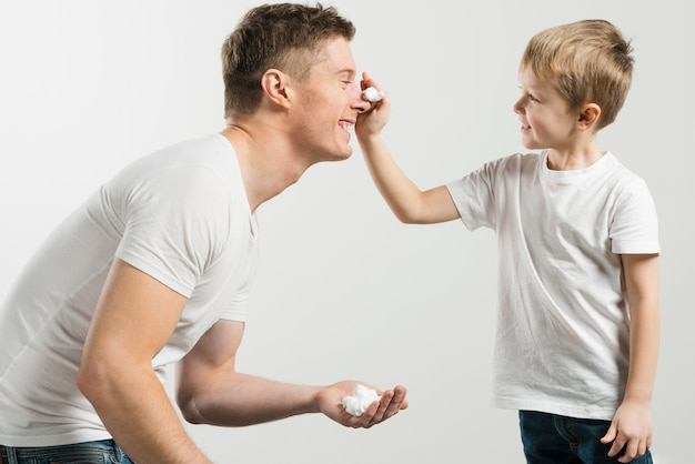 Father and son playing with shaving foam against white background