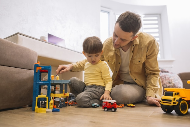 Father and son playing with trucks and lego pieces