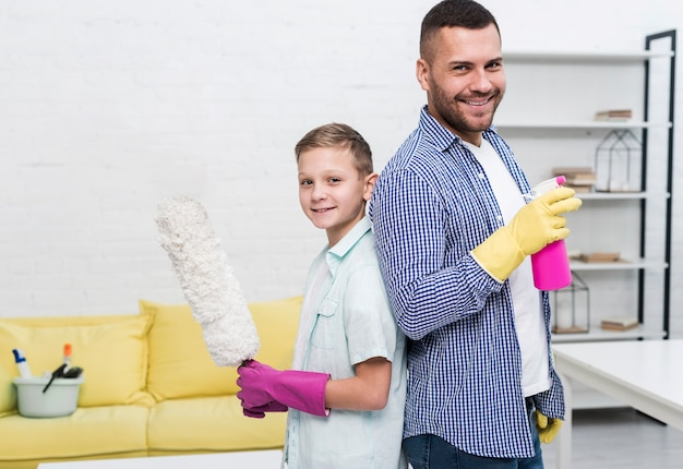 Father and son posing back to back with cleaning products