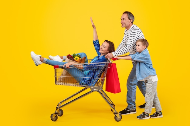 Father and son pushing shopping cart with mother
